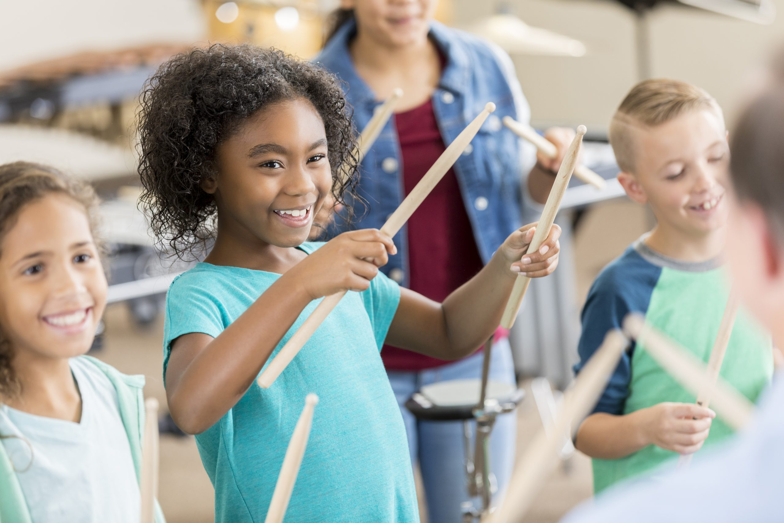 Excited diverse schoolchildren holds drumsticks during percussion class.